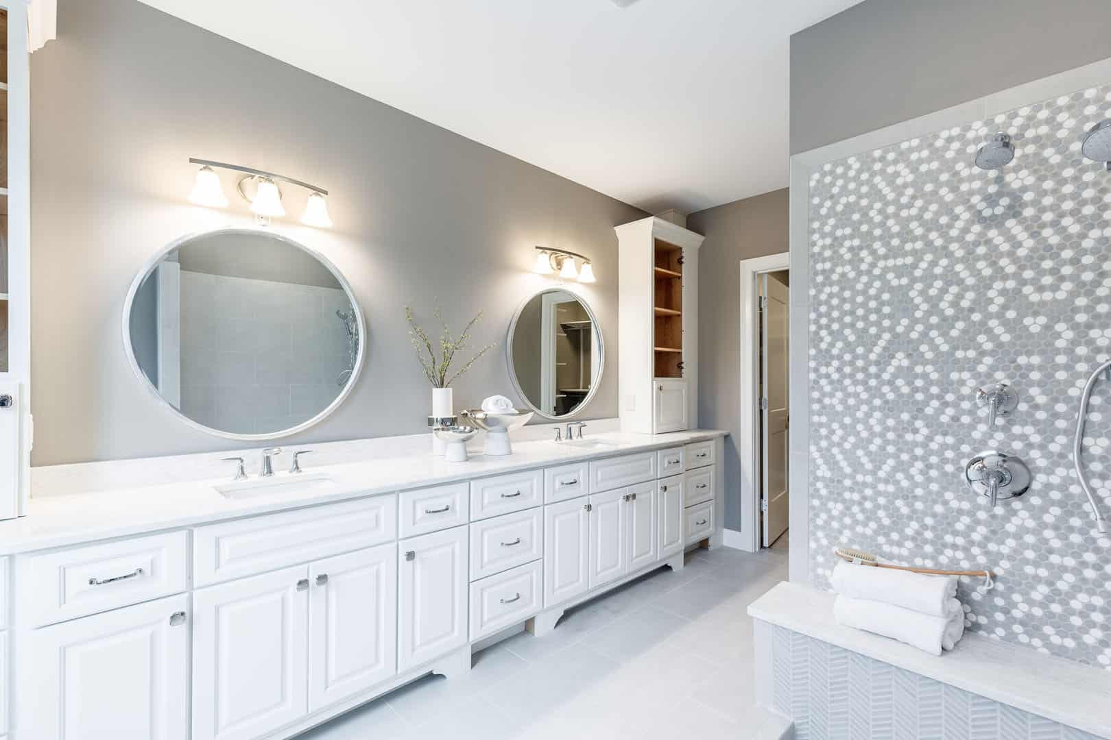 large bathroom with tile shower and white double vanity