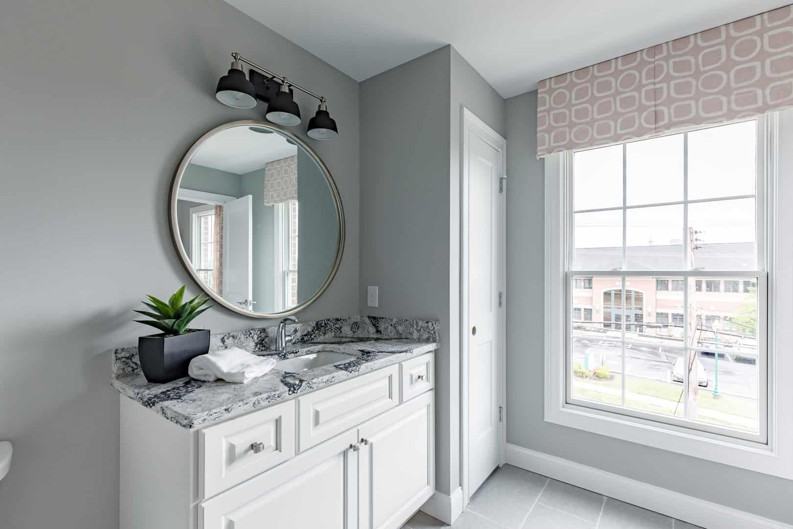 round mirror above white bathroom vanity