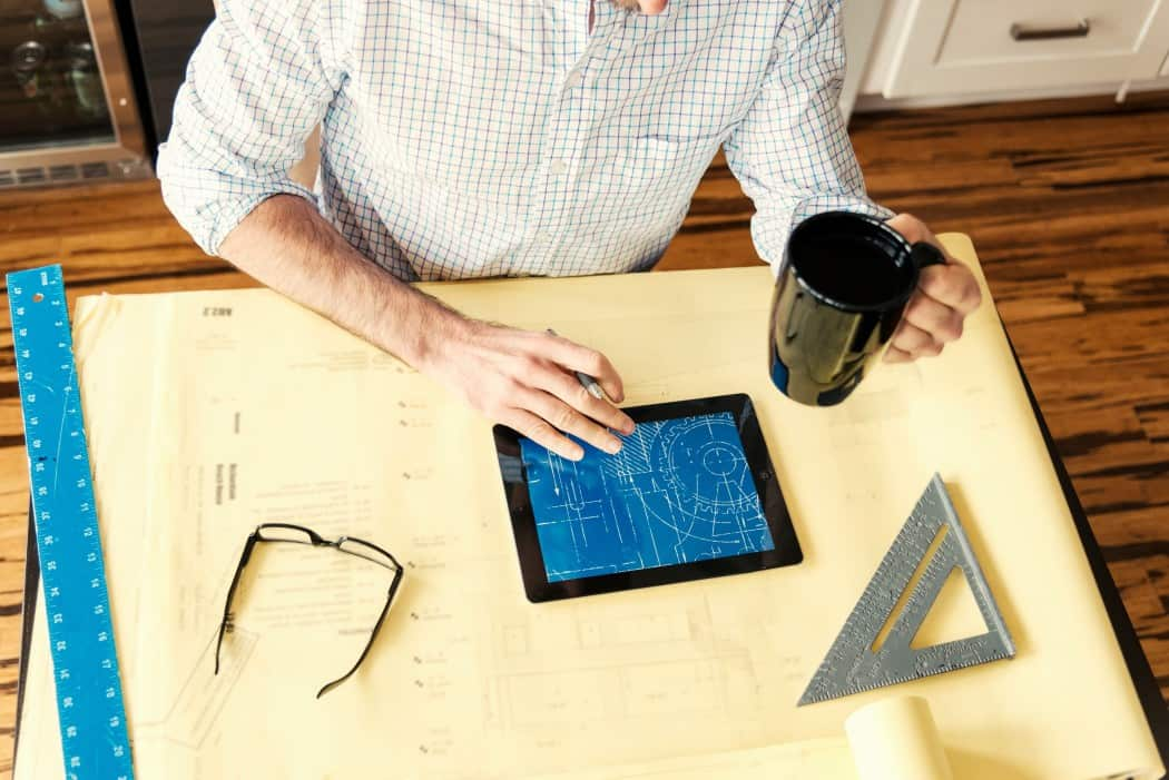 person holding coffee while working on a blueprint on an iPad