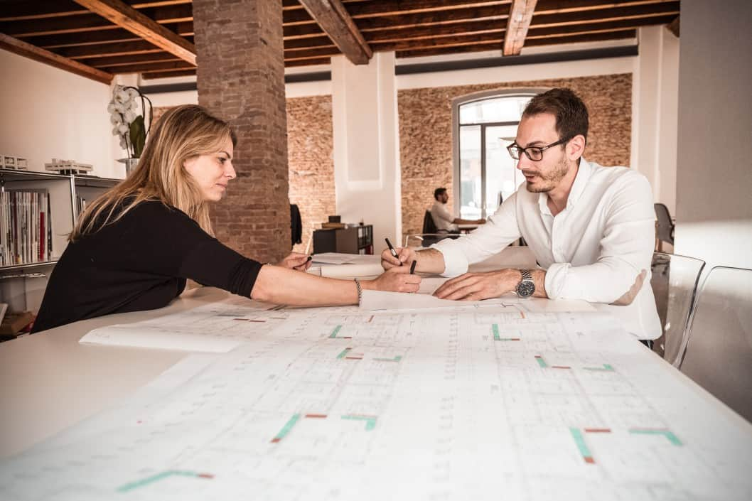 a man and a woman looking over a blueprint together